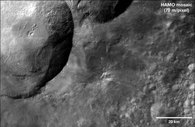 This mosaic from NASA's Dawn spacecraft shows dark material near a series of craters known as the 'snowman' on asteroid Vesta. That ejected material is a complex mixture of components.