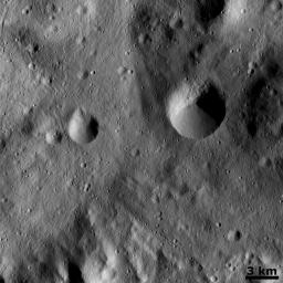 This image from NASA's Dawn spacecraft show a slightly curved chain of small craters in the bottom half of the image. This chain is located on the floor of asteroid Vesta's large south-polar impact structure, Rheasilvia.