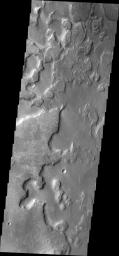 This image from NASA's 2001 Mars Odyssey spacecraft shows the floor of an unnamed crater east of Aram Chaos and Ares Vallis. There are two distinct elevations on the crater floor, which may indicate layered fill material.