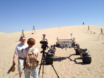 Michael Malin, left, principal investigator for three science cameras on NASA's Curiosity Mars rover, comments to a news reporter during tests with Curiosity's mobility-test stand-in, Scarecrow, on Dumont Dunes in California's Mojave Desert.