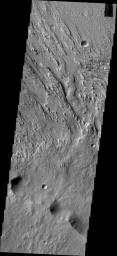This image from NASA's 2001 Mars Odyssey spacecraft shows two directions of wind erosion southwest of Olympus Mons and south of Elysium Mons.