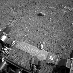 This image shows a close-up of track marks from the first test drive of NASA's Curiosity rover. The rover's arm is visible in the foreground. A close inspection of the tracks reveals a unique, repeating pattern: Morse code for JPL.