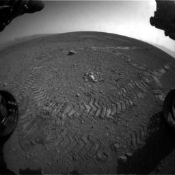 This image shows the tracks left by NASA's Curiosity rover on Aug. 22, 2012, as it completed its first test drive on Mars. This image was taken by a front Hazard-Avoidance camera, which has a fisheye lens.