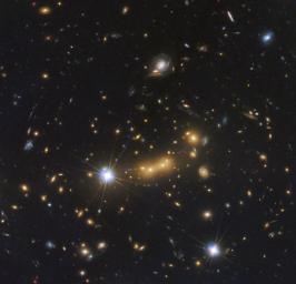 In this Hubble observation, astronomers used the massive galaxy cluster MACS J0647+7015 as the giant cosmic telescope. The bright yellow galaxies near the center of the image are cluster members.