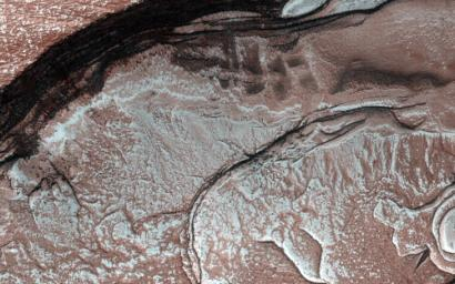 Sunlight was just starting to reach the high Northern latitudes in late winter when NASA's Mars Reconnaissance Orbiter's HiRISE camera captured this image of part of the steep scarps around portions of the North Polar layered deposits.
