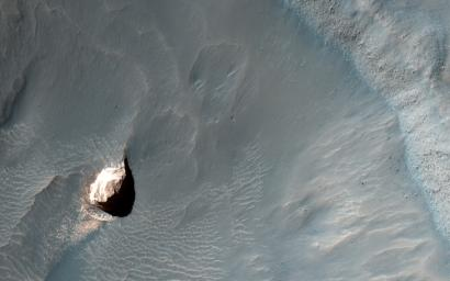 This observation captured by NASA's Mars Reconnaissance Orbiter shows a small crater in within the much larger Pollack Crater containing light-toned material.