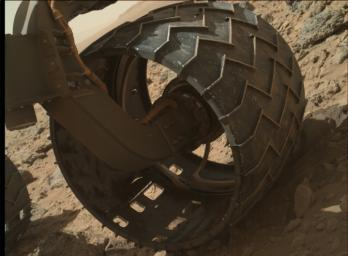The left-front wheel of NASA's Curiosity Mars rover shows dents and holes in this image taken by the MAHLI camera, which is mounted at the end of Curiosity's robotic arm.