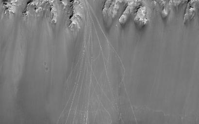 When boulders roll down a dusty Martian slope, they can leave long, dotted tracks behind on the slope surface as seen in this observation from NASA's Mars Reconnaissance Orbiter.