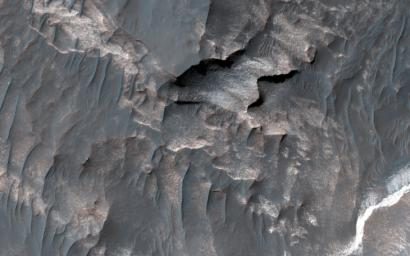 NASA's Mars Reconnaissance Orbiter shows light-toned deposits along Coprates Chasma slopes.