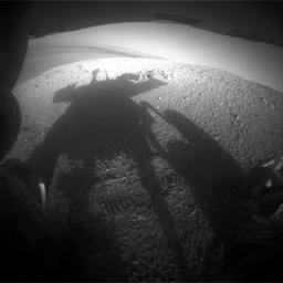 NASA's Mars Exploration Rover Opportunity caught its own silhouette in this late-afternoon image from the rover's rear HAZCAM on Mar, 20, 2014; its shadow falls across a slope called McClure-Beverlin Escarpment on the western rim of Endeavour Crater.