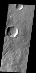 Several channels are located on the flank of Hecates Tholus. In this image captured by NASA's 2001 Mars Odyssey spacecraft, one of those channels enters a crater, creating a deposit on the floor of the crater.