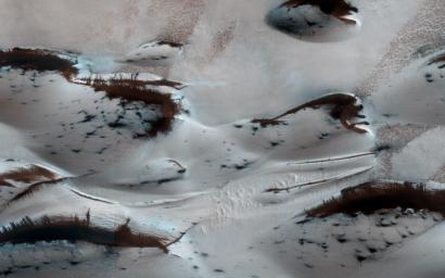 NASA's Mars Reconnaissance Orbiter shows Mars' northern-most sand dunes beginning to emerge from their winter cover of seasonal carbon dioxide (dry) ice. Dark, bare south-facing slopes are soaking up the warmth of the sun.