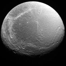 Cracks, canyons, craters, and streaks are seen in this image of Saturn's icy moon, Dione, taken from Voyager 2 on August 3, 2005.