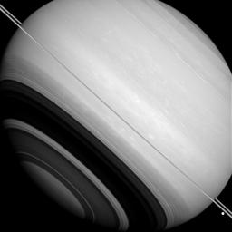 NASA's Cassini orbiter shows Saturn is circled by its rings (nearly edge-on in this image), as well as by the moons Tethys (the large bright body near the lower right corner) and Mimas (seen as a slight crescent against Saturn's disk above the rings).