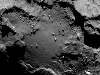 Close up detail focusing on a smooth region on the 'base' of the 'body' section of comet 67P/Churyumov-Gerasimenko. The image was taken by ESA's Rosetta's OSIRIS on August 6, 2014.