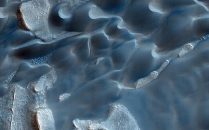 The deep chasm that formed on the polar cap edge is identified as an area of strong down-slope winds and has a clear connection to Mars' largest dune field, Olympia Undae as observed by NASA's Mars Reconnaissance Orbiter.