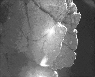 From the location where it came to rest after bounces, the Philae lander of the European Space Agency's Rosetta mission captured this view of a cliff on the nucleus of comet 67P/Churyumov-Gerasimenko. The feature is called 'Perihelion Cliff'.