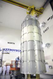 In the Astrotech payload processing facility on Vandenberg Air Force Base in California, technicians secure a transportation canister around NASA's Soil Moisture Active Passive (SMAP) spacecraft for its move to the launch pad.