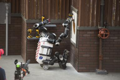 Using a cordless power drill, RoboSimian cuts a hole into a panel of drywall to complete one of the tasks in the DARPA Robotics Challenge Finals.