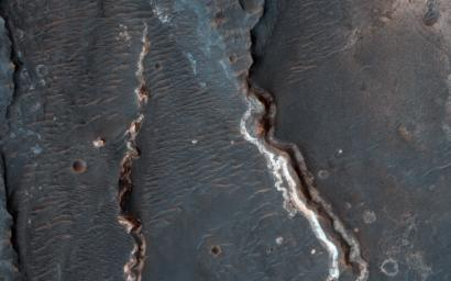 This observation from NASA's Mars Reconnaissance Orbiter shows an interesting crater floor with what appear to be inverted channels, rounded lobe-like landforms, and light-toned layered deposits along the southern portion of the crater wall.