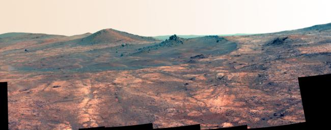 An elongated crater called 'Spirit of St. Louis,' with a rock spire in it, dominates this false-color image from the panoramic camera (Pancam) on NASA's Mars Exploration Rover Opportunity.
