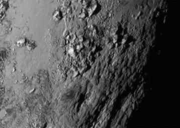 This close-up image from NASAs New Horizon spacecraft is of a region near Pluto equator reveals a giant surprise: a range of youthful mountains rising as high as 11,000 feet 3,500 meters above the surface of the icy body.