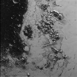 A newly discovered mountain range lies near the southwestern margin of Pluto's heart-shaped Tombaugh Regio (Tombaugh Region), situated between bright, icy plains and dark, heavily-cratered terrain as seen by NASA's New Horizons spacecraft.