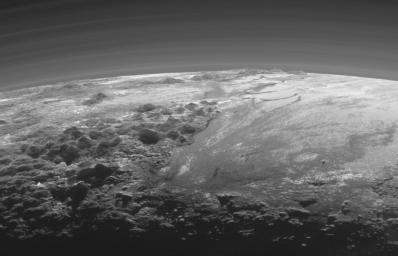 Just 15 minutes after its closest approach to Pluto on July 14, 2015, NASA's New Horizons spacecraft looked back toward the sun and captured a near-sunset view of the rugged, icy mountains and flat ice plains extending to Pluto's horizon.