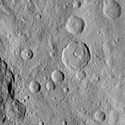 This image of Ceres, taken by NASA's Dawn spacecraft, shows a 23-mile-wide (37 kilometer-wide) crater called Tupo, which features a curved central peak complex and terraces.