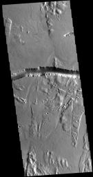 The depression crossing this image from NASA's 2001 Mars Odyssey spacecraft is a lava channel called Olympica Fossae. It is located on lava plains between Alba Mons and Olympus Mons.