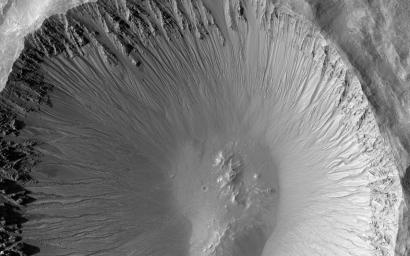 The central portion of this image is dominated by a sharp-rimmed crater that is roughly 5 kilometers in diameter. On its slopes, gullies show young (geologically recent) headward erosion, which is the lengthening of the gully in the upslope direction.