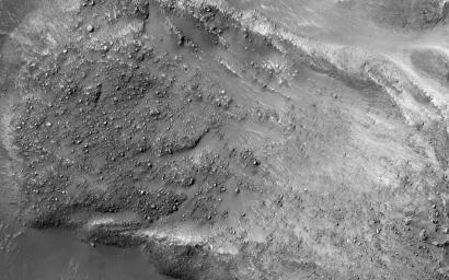 The striking feature in this image from NASA's Mars Reconnaissance Orbiter is a boulder-covered landslide along a canyon wall. Landslides occur when steep slopes fail, sending a mass of soil and rock to flow downhill, leaving a scarp atop the slope.