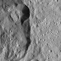 This view captured by NASA's Dawn spacecraft shows a section of Jarimba Crater on Ceres. A portion of the crater rim near top center appears much sharper, with smoother walls, than elsewhere.