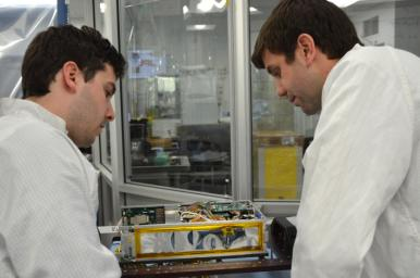 Engineers for NASA's MarCO technology demonstration inspect one of the two MarCO CubeSats. Cody Colley, MarCO integration and test deputy, left, and Andy Klesh, MarCO chief engineer, are on the team at NASA's Jet Propulsion Laboratory, Pasadena, CA.
