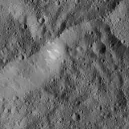 This scene from Ceres, captured by NASA's Dawn spacecraft, shows an older crater (at top center) that has been blanketed by impact ejecta from the younger crater to its right.