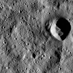 This image from NASA's Dawn spacecraft shows a fresh impact crater with an asymmetric rim. The crater displays a sharp rim over much of its perimeter that is interrupted by a smooth area in the north.