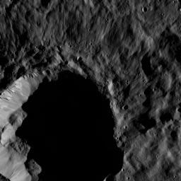 This view from NASA's Dawn spacecraft shows a moderate-sized impact feature that is imprinted upon the southern rim of Mondamin Crater. Boulders of various sizes can be seen around the crater's rim and on the sunlit part of its floor.
