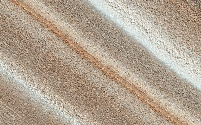 The North Polar layered deposits provide a record of recent climate changes on Mars as seen by NASA's Mars Reconnaissance Orbiter spacecraft. Color variations between layers are due to differences in composition of the dust.