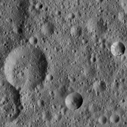 This picture from NASA's Dawn spacecraft shows two relatively fresh craters within older, highly cratered terrain on Ceres. The young crater at right shows some spurs of compacted material along its rim, as well as some bright streaks along its flanks.