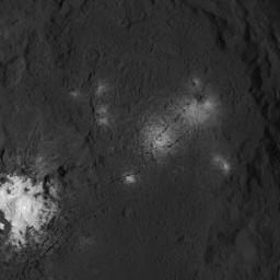 The iconic bright spots of Occator Crater are seen up close in this image of Ceres. This image from NASA's Dawn spacecraft reveals a central dome with linear features on and around it.