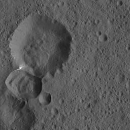 Two adjoining craters on Ceres are featured in this image from NASA's Dawn spacecraft. A lobe-shaped feature is prominent in the larger crater's interior. Bright material is visible at the intersection of the two craters.