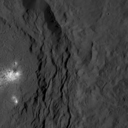 A cluster of bright areas in Ceres' Occator Crater are seen in this image from NASA's Dawn spacecraft. These areas are not as bright as the material at the center of the crater.