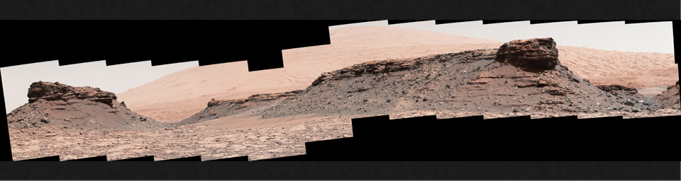 The two prominent mesas in this view of Mars' 'Murray Buttes' region from NASA's Curiosity Mars rover are about 260 feet (about 80 meters) apart. Upper Mount Sharp is the salmon-hued mound dominating the horizon between the scene's two prominent mesas.
