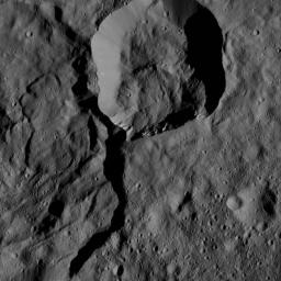 NASA's Dawn spacecraft views a crater at top center that touches the rim of Messor Crater (25 miles, 40 kilometers), shown at left.