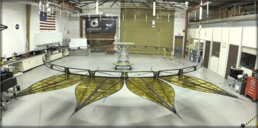 This image shows a deployed half-scale starshade with four petals at NASA's JPL. On a starshade ready for launch, the thermal gold foil will only cover the side of the petals facing away from the telescope.