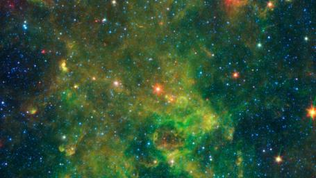 An age-defying star called IRAS 19312+1950 stands out as extremely bright inside a large, chemically rich cloud of material, as shown in this image from NASA's Spitzer Space Telescope.