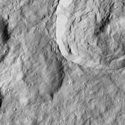 This image from NASA's Dawn spacecraft shows a crater at upper right with a sharply defined rim. To its left is an older impact crater whose features have been softened by a blanket of material, likely ejected from a nearby impact.