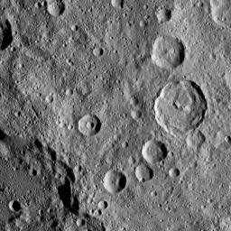 In this densely cratered area of Ceres, NASA's Dawn spacecraft spotted Tupo Crater, with its complex, hummocky interior, at center right. A portion of the rim of Darzamat Crater appears with dark shadows at lower left.