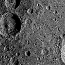 Sintana Crater is seen on the left side of this image of Ceres from NASA's Dawn spacercraft. The crater's central peak casts a shadow over its western flank. At lower right, the rim of Darzamat peeks into view.