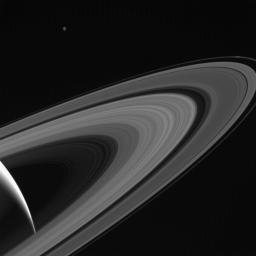 NASA's Cassini gazes across the icy rings of Saturn toward the icy moon Tethys, whose night side is illuminated by Saturnshine, or sunlight reflected by the planet.